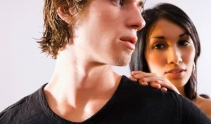 Close-up of serious young man glancing back at young woman